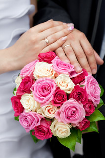 the hands of the bride and groom lying on the bridal bouquet