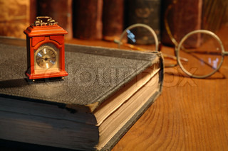 Vintage still life. Small wooden clock standing on old book on background with books and spectacles