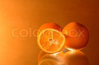 Three oranges lying on glass on nice background with copy space