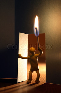 Yellow plasticine man with lighting match entering to dark room. Conceptual composition with open door made from paper