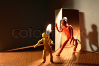 Few plasticine men with lighting match entering to dark room. Conceptual composition with open door made from paper