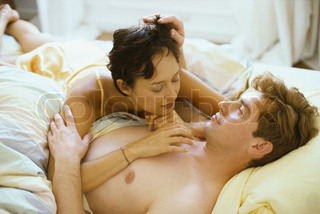 ?John Dowland/AltoPress/Maxppp ; Couple lying in bed together, woman resting on man's chest