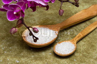 Spa essentials (bath salt in a spoon and flowers of orchids)