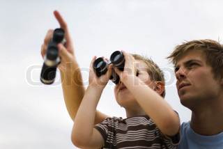 ?Ale Ventura/AltoPress/Maxppp ; Father and son using binoculars, man pointing skyward