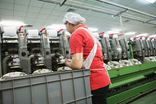 ?James Hardy/AltoPress/Maxppp ; Worker tending spooling frames in cotton mill, Guangdong province, China