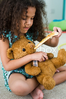 ?Laurence Mouton/AltoPress/Maxppp ; Little girl feeding teddy bear pizza