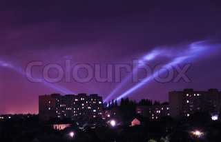 night sky over city in lights of projectors