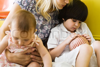 ?Laurence Mouton/AltoPress/Maxppp ; Mother holding son and infant daughter on lap, boy sulking, cropped