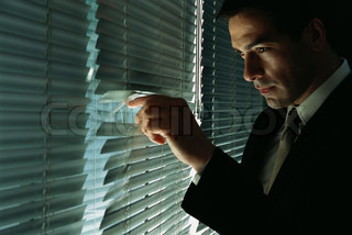 ?Laurence Mouton/AltoPress/Maxppp ; Man in suit discreetly looking through blinds out window