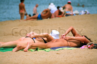 Two girls sunbathing on a beach at water