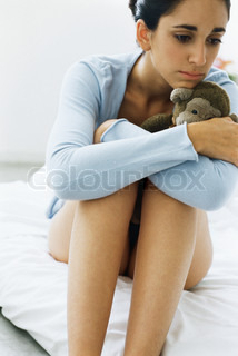 ?Laurence Mouton/AltoPress/Maxppp ; Young woman hugging knees, holding stuffed monkey, despondently looking away