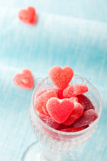 Heart shape candy in a glass for Valentine's day on a light blue background