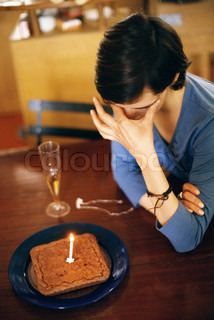 ?John Dowland/AltoPress/Maxppp ; Woman sitting at table alone with anniversary cake, covering eyes