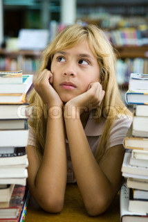?Sigrid Olsson/AltoPress/Maxppp ; Preteen girl sitting with two large stacks of books, chin in hands, looking away
