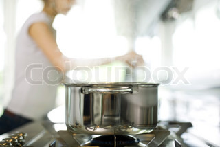 ?Laurence Mouton/AltoPress/Maxppp ; Pot cooking on stove, woman in background