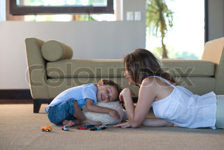 ?Eric Audras/AltoPress/Maxppp ; Mother and young son together in living room playing, boy hugging stuffed toy