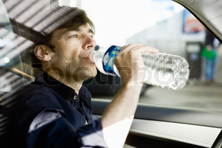 ?Philippe Dureuil James Hardy/AltoPress/Maxppp ; Man drinking bottled water while driving