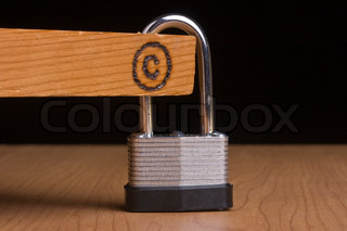 Copyright symbol on a piece of wood that is attached to a lock.