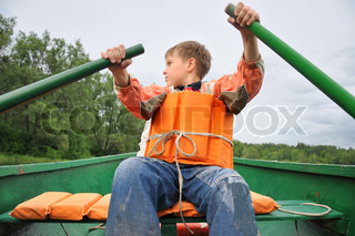 Young man rowing a boat on the river.