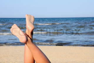 lovely legs on the beach on blue sky