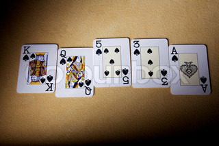 A royal straight flush playing cards poker hand in peak. Cards for game in poker. Cards on a table for game in poker. A fan from cards