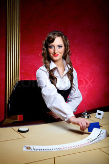 The beautiful girl dealer behind a table for game in poker