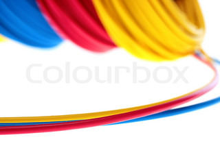 Electric wires of red, yellow and dark blue colour are winded in ...