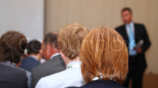 The image of red-hairedsitting man at the seminar