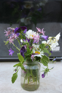 The image of bouquet in the glass pot. Focus is under the  centre of the image