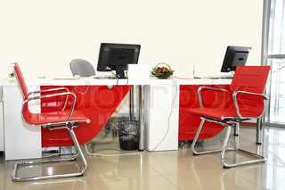 The image of empty office room with red and white chairs and table
