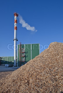 Mountain of wood sawdust against the blue sky and the factory pipe which are letting out a smoke