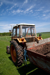 Tractor with trailer in countryside with blue sky