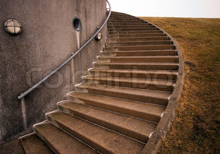 Spiraling stairs outdoors close to building and dike, Denmark.