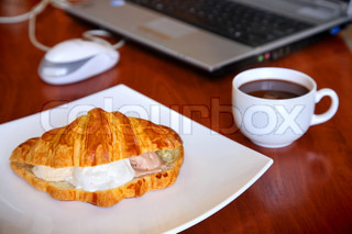 Hot coffee and croissant with ice-cream on office table with the laptop