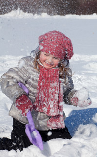 The girl in pink cap and scarf plays with a shovel on snow