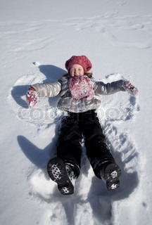 The smiling girl in pink cap and scarf lays on snow