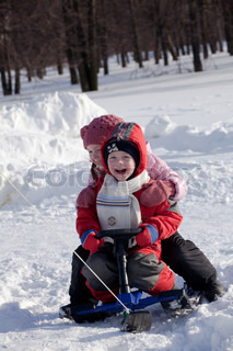 The girl dressed in a white jacket both a pink cap and a scarf, and her brother in red winter overalls ride a snow-scooter