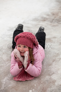 The smiling girl in pink cap and scarf slides on icy descent