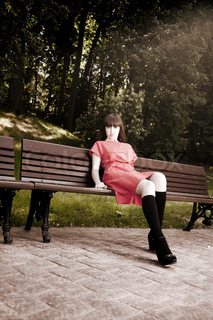 Beauty Woman Sitting On A Park Bench Under the Sunlight