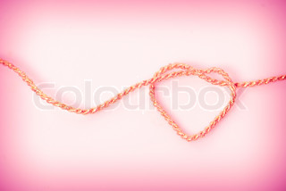 Heart shape from gold rope on pink background. Love postcard
