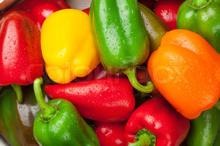 Fresh colorful bell peppers on wooden table