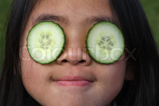 close up of child face with cucumber slice on the eyes
