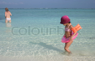 sceneries from the maldivian islands: girl and mother in the turquoise color water