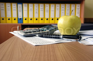 office desk papers, calculator, pen and apple
