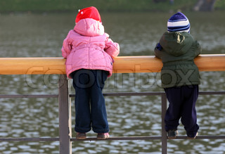 The boy and the girl observe of a watercourse, standing on a quay protection, are visible from a back