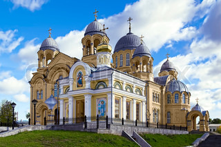 Holy Cross Cathedral, with gray zinc dome and the Chapel of St. Nicholas Monastery in the background of blue sky and white clouds (Verhoturie city of Sverdlovsk Region)