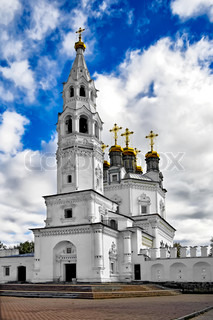 White Stone Holy Trinity church tower with gold baths and crosses against the blue sky, white clouds (Verhoturie city of Sverdlovsk Region)