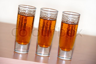 three small glasses of brown alcohol drink closeup
