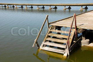 old wooden stairs on yellowish lake at Palic, Serbia