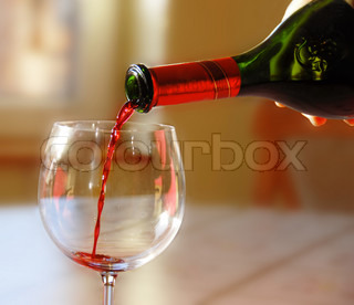 Pouring red wine into wineglass from green bottle